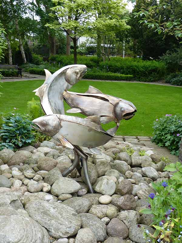 a statue of fish in a garden